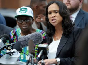 Baltimore State's Attorney Marilyn Mosby, right, holds a press conference near the site where Freddie Gray was arrested after her office dropped the remaining charges against three Baltimore police officers awaiting trial in Gray's death. Gray's stepfather, Richard Shipley, is pictured left. Image by Steve Rurak/AP