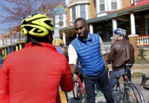 Black Lives Matter activist DeRay McKesson talks with cyclists in the Charles Village neighborhood of Baltimore. Photo courtesy of Patrick Semansky/AP.
