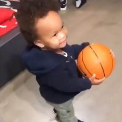 Toddler carries basketball in Nike store